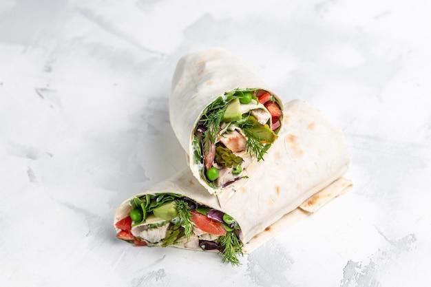 新鮮なトルティーヤは、野菜のアスパラガス、アボカド、トマト、エンドウ豆、チーズ、タルタルで包みます