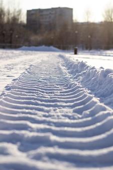 겨울에 눈 속에서 트랙터의 신선한 트랙. 제설