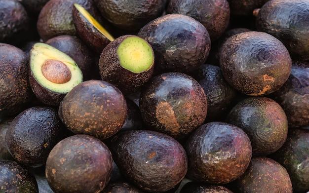 Свежие тропические фрукты авокадо крупным планом для продажи на рынке, хорошо для фона