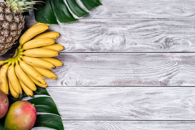 木の上面図に新鮮なトロピカルフルーツ。バナナ、パイナップル、ココナッツ、マンゴー、ライチ、栗。