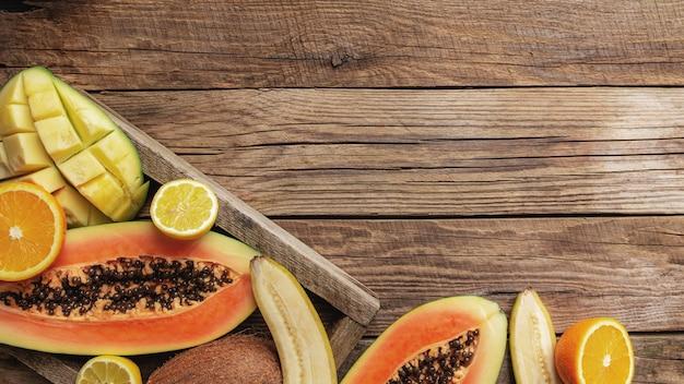 Свежие тропические фрукты в деревянной коробке доставки на деревянном столе. папайя, апельсин, банан, кокос, манго и лимон, вид сверху.