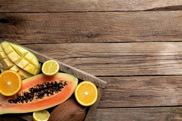 Свежие тропические фрукты в деревянной коробке доставки на деревянном столе. папайя, апельсин, кокос, манго и лимон, вид сверху.