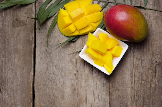Fresh tropical mango on wooden table.