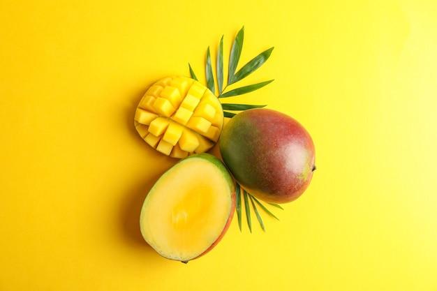 Свежие тропические спелые манго на цветном фоне, вид сверху