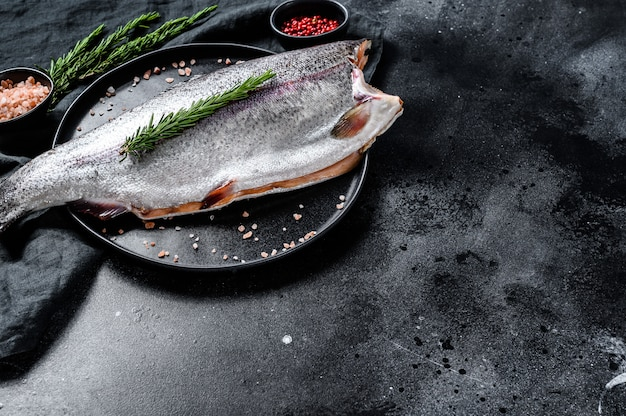 Fresh trout fish with salt and rosemary. top view.