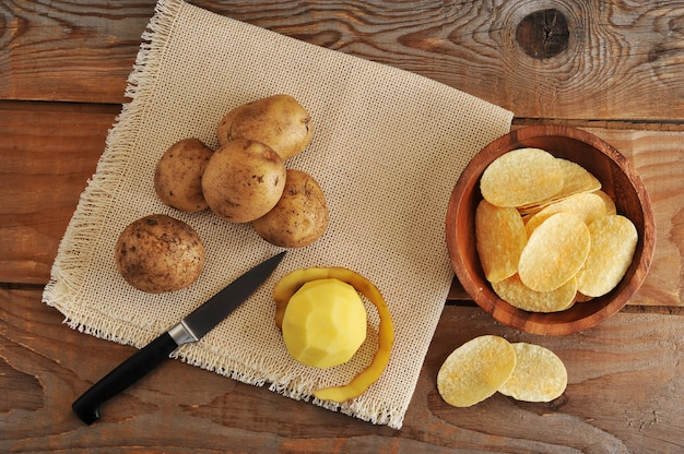 Fresh tubers of potato, knife for cleaning of potatoes and potato chips