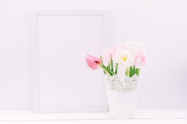 Fresh tulip flowers in vase with blank photo frame