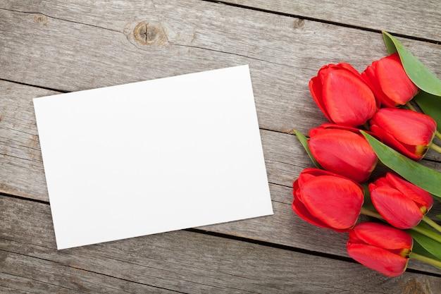Свежие тюльпаны и открытка на фоне деревянного стола