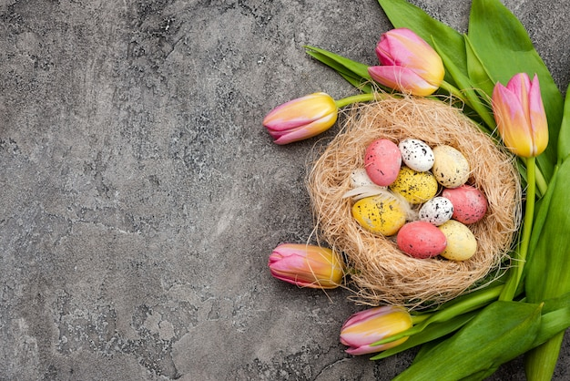 Fresh tulips and colorful eggs in the nest