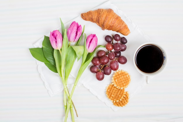 Fresh tulips; croissant; grape fruits; waffles and tea cup on white background