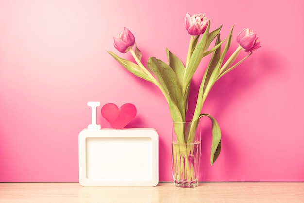 Fresh tulips flowers in glass vase on table