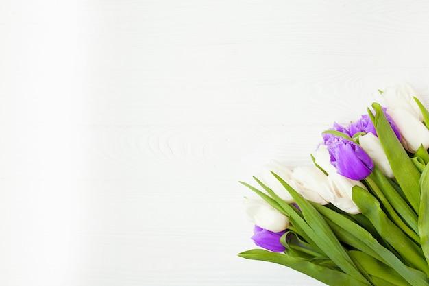 母の日のための白い木製の背景に新鮮なチューリップ