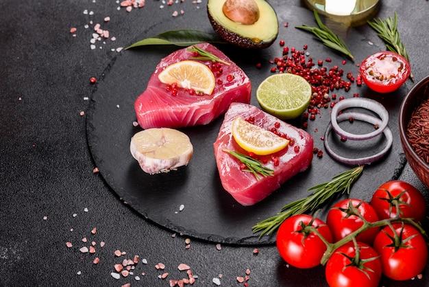 スパイスと黒の背景にハーブと新鮮なマグロの切り身ステーキ。マグロを焼くための準備