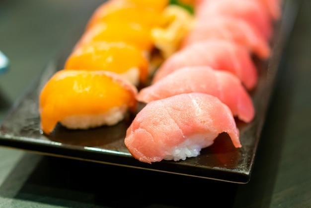 Сырые суши из свежего тунца на тарелке - стиль японской кухни