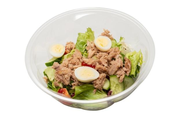 プラスチック容器にレタス、キュウリ、さくらんぼ、卵を入れた新鮮なツナサラダ。上面図。