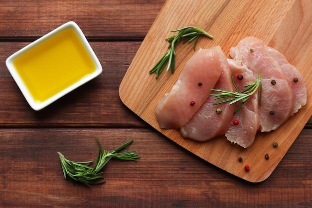 ボウルにローズマリースパイスペッパーミックスとオリーブオイルを入れた新鮮な七面鳥の切り身