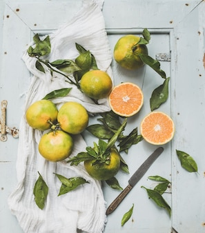 Fresh turkish tangerines with leaves over blue rustic wooden surface, top view.