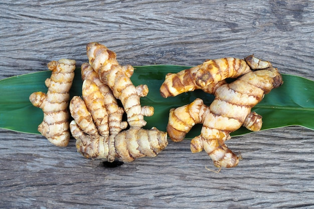 Fresh turmeric with green leaf on old wooden table