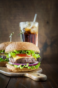 Fresh two beef burgers with cola on wooden board