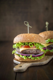Fresh two beef burgers with vegetables on wooden board
