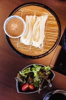 참깨 소스와 함께 신선한 우동 샐러드와 함께 대나무 매트에 재직했습니다.