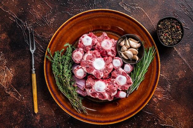 Свежая сырая говядина бычьи хвосты нарезанное мясо на деревенской тарелке с зеленью