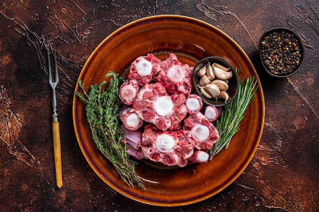 Fresh uncooked beef oxtail cut meat on rustic plate with herbs