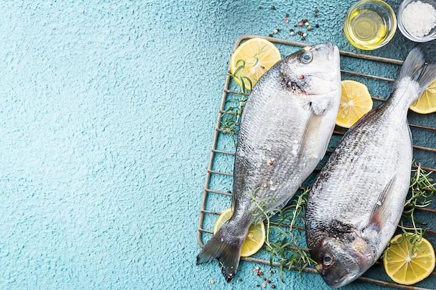Свежая сырая рыба дорадо или морской лещ на гриле с ломтиками лимона и зеленью на синей поверхности, вид сверху