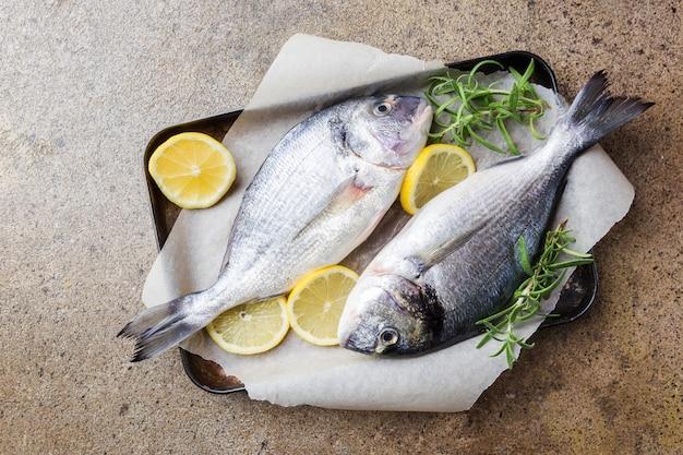 新鮮な未調理のドラドまたは鯛の魚、材料、レモン、ローズマリーを紙に