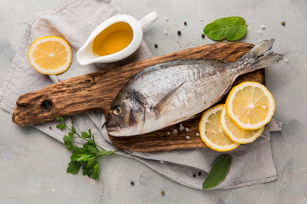 Fresh uncooked fish on wooden board with lemon slices