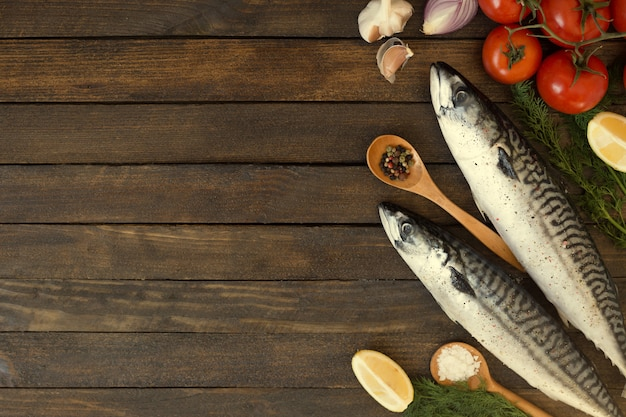 Fresh uncooked mackerel fish with lemon, herbs, oil, vegetables and spices on rustic wooden board