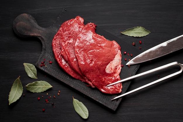 Свежее сырое мясо на деревянной доске с ножом и зеленью