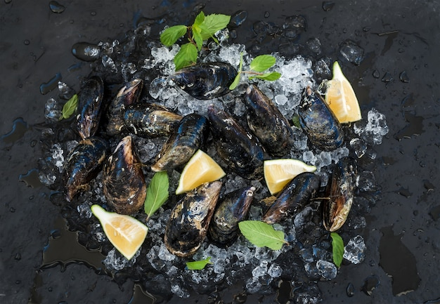 Fresh uncooked mussels with lemon, herbs and spices on chipped ice over dark slate stone