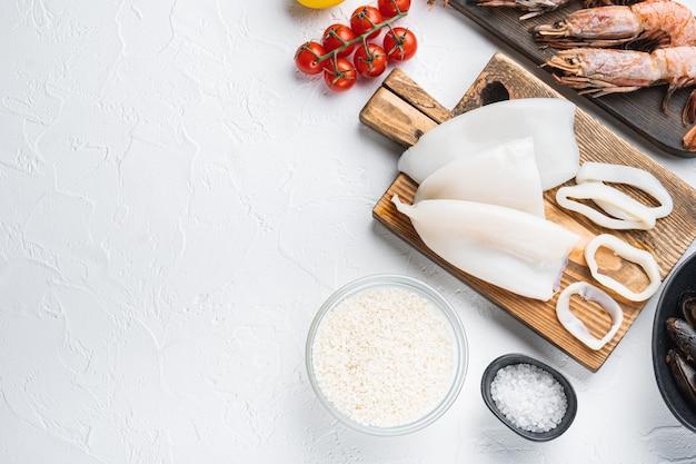 Свежие сырые блюда из морепродуктов и рис для испанской паэльи на белом текстурированном фоне, плоская планировка с копией пространства, фото еды.