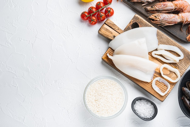 Fresh uncooked sea food specialties and rice for spanish paella on white textured background, flat lay with copy space, food photo.