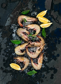 Fresh uncooked shrimps with lemon, herbs and spices on chipped ice over dark slate stone