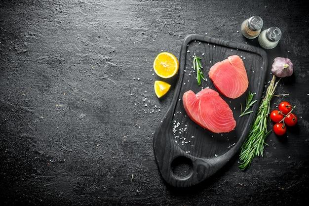 Свежий сырой стейк из тунца на разделочной доске с помидорами, розмарином, чесноком, специями и лимоном. на черном деревенском