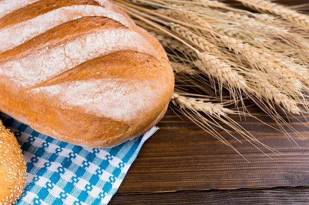 木製のテーブルの上に黄金の熟した小麦の耳を持つ新鮮なノーカットの大きな無愛想なフランスパン、クローズアップビュー