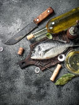 소박한 테이블에 화이트 와인과 신선한 준비되지 않은 도라도 물고기.