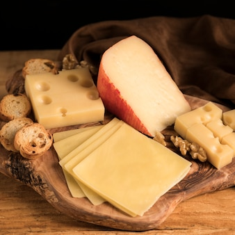 Fresh variety of cheeses with walnut and bread on wooden textured tray