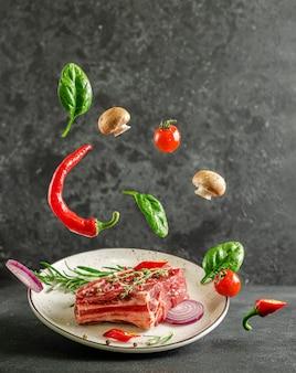 Свежий стейк из телячьей кости на тарелке с летающими ингредиентами для приготовления на темном фоне