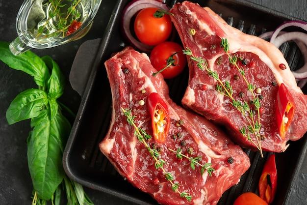 Свежие стейки из телячьей кости на сковороде для гриля со специями и зеленью