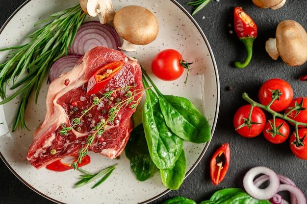 향신료와 허브와 함께 접시에 신선한 송아지 뼈 스테이크. 요리 개념. 평면 위치, 평면도