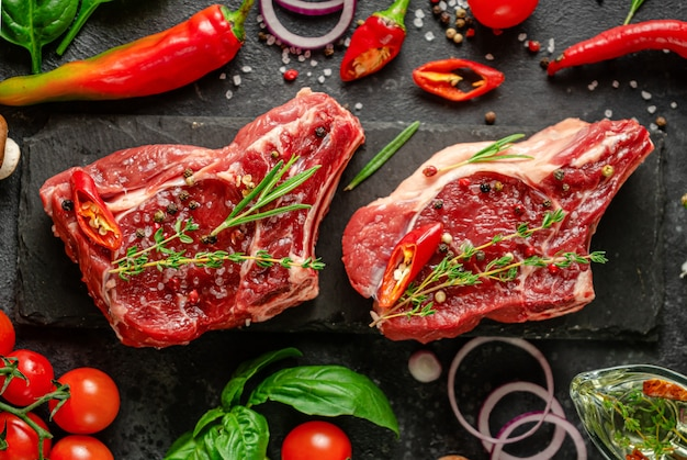 Fresh veal bone steaks with spices, vegetables and herbs on dark background. flat lay, close up.
