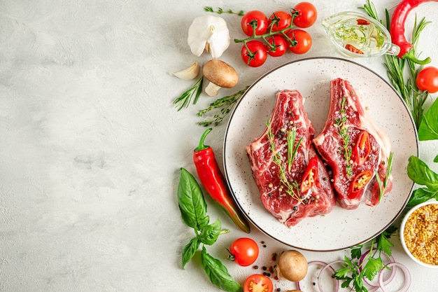 Fresh veal meat with various ingredients for cooking on concrete background. flat lay, copy space.