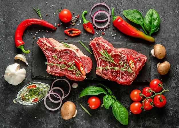 Свежие стейки из телятины со специями, овощами и зеленью на темном фоне