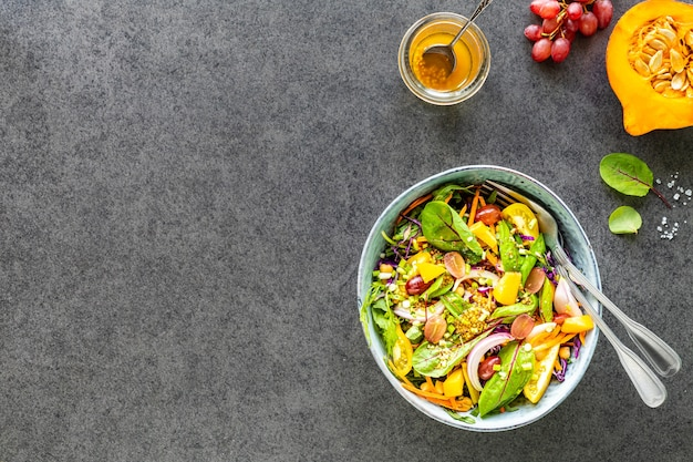 黒い石のテーブルの上の皿に新鮮な野菜と果物のサラダ。上面図