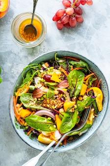 白い石の表面のプレートに新鮮な野菜とカボチャのサラダ。上面図