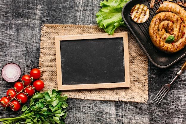 회색 질감 배경에 빈 슬레이트와 신선한 야채와 나선형 구운 소시지
