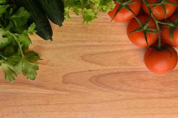 新鮮な野菜の国境は、自然な木製の背景に設定します。メニューやレシピのモックアップ。水滴と野菜。
